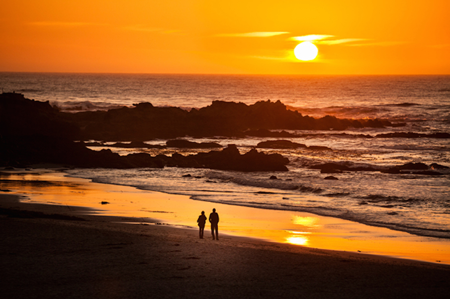 People stroll on the sand beach by the Pacific Ocean coastline in Carmel California near Monterey